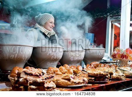 Kyiv Ukraine - Jan 8 2017: Woman sell mulled wine at traditional Christmas market on Sophia Square in Kyiv. There are many stalls selling gifts and also serving up seasonal food and drink