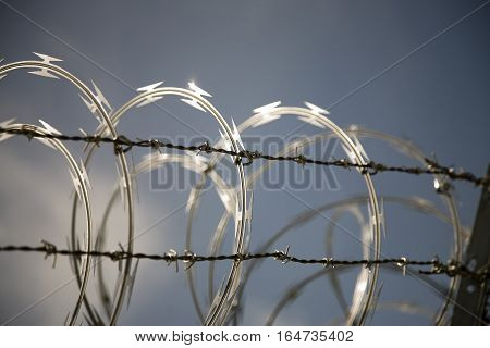 Twisted Barbed Wire On A Background Of Blue Sky.