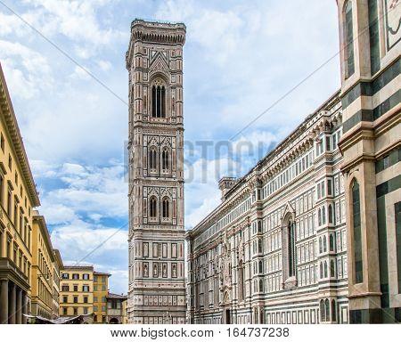 Giotto's Campanile at the Basilica of Santa Maria del Fiore. Blue cloidy sky. Piazza del Duomo in Florence Italy.