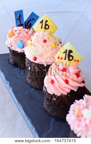 Pink cupcake with number sixteen on top