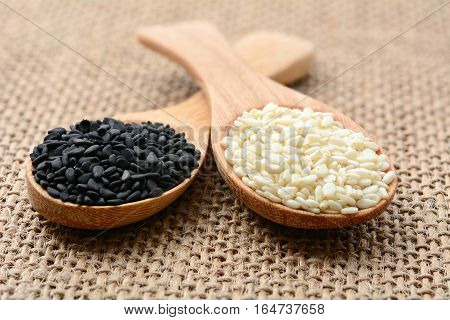 Black sesame and white sesame seeds on wooden spoon and on sackcloth
