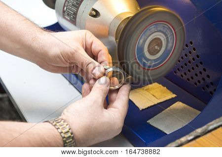 Male hands polishing a time piece body on a special machine closeup selective focus shot