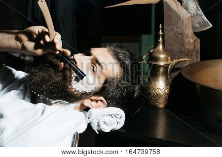 Handsome bearded man hipster brunette with beard and moustache has shave in barbershop. Barber works with vintage razor shaving brush and foam