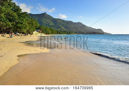 Beautiful sandy beach Beau Vallon one from the most popular beaches at the island of Mahe at sunset SEYCHELLES