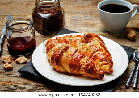 fresh Breakfast with croissants espresso and jam on a wood background.