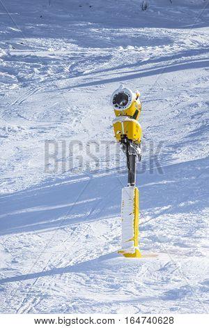 Snow cannon. Snowmaking in winter mountain. Snow gun on ski slopes.