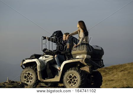 Handsome man and two pretty girls ride quad bike on field road on natural background