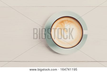 Cappuccino with frothy foam, blue coffee cup top view closeup on white wood background. Cafe and bar, barista art concept. Filtered
