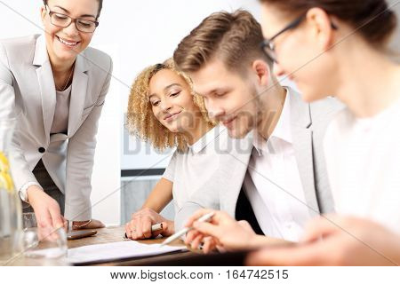 Business consultants while working in a team. The team of employees at work. A group of young workers at a meeting in the company conference room