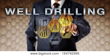 Male industry manager in blue business suit is touching WELL DRILLING on an interactive virtual control monitor. Oil and gas industry technology concept for the process of borehole drilling.
