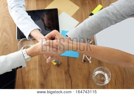 Teamwork, success in business. Hands of four people in a gesture of success, victory. Motivation, teamwork on the project. Hands of four people in a gesture of success, victory