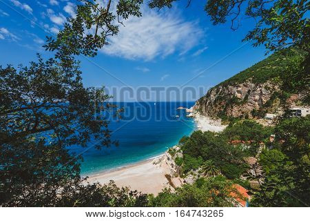 Adriatic sea coast by sunny day summer landscape. Pebble beach, house roofs and green tree brunches under blue sky near Perazica Do village on the way to Petrovac, Montenegro.