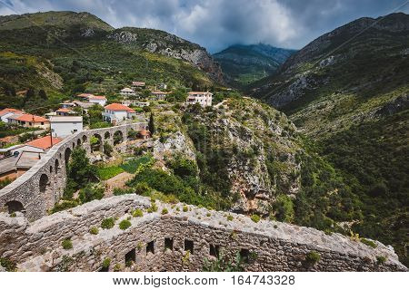 Rocks, ancient stone aqueduct and fortress wall of Old Bar town, Montenegro. Stari Bar - ruined medieval city on Adriatic coast, Unesco World Heritage Site.