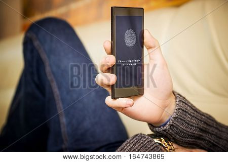 Fingerprint scanning for secure access. A young man with a mobile while lying on the couch.