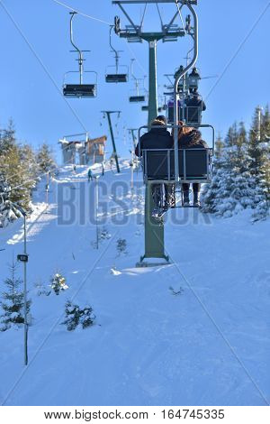 People on holiday coming to ski use the cable car to reach the summit