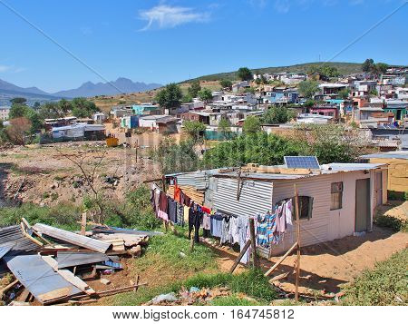Informal settlement - Enkanini with mountain and blue sky on the outskirts of Stellenbosch, Western Cape province, South Africa. Many shacks in Enkanini have solar panels for access to electricity. poster