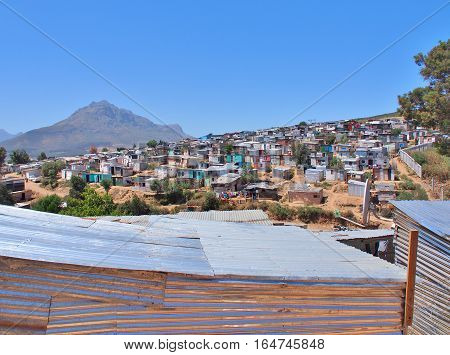 Informal settlement - Enkanini with mountain and blue sky on the outskirts of Stellenbosch, Western Cape province, South Africa. Many shacks in Enkanini have solar panels for access to electricity.