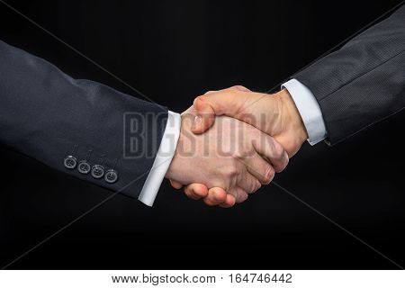 Close-up partial view of businespeople shaking hands on black