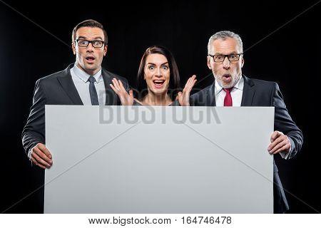 Three surprised businespeople holding blank card on black