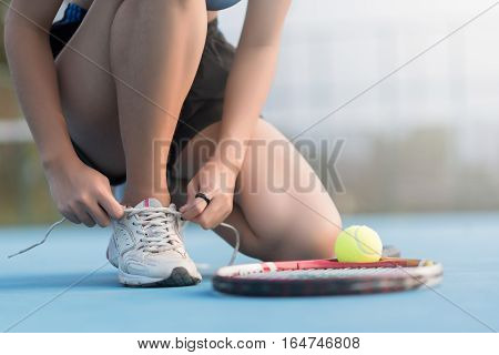 Tennis player tying shoelaces in tennis court at Thailand.