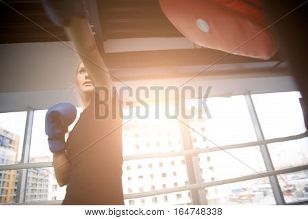 Young sportswoman boxing at gym in sports clothing