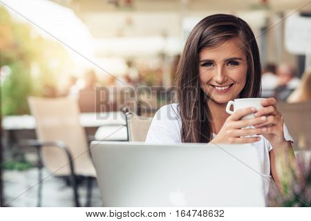 Portrait of an attractive young brunette woman sitting at a sidewalk cafe using a laptop and drinking a cup of coffee