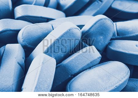Blue pills as background, close - up