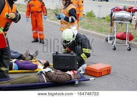 CZECH REPUBLIC, PLZEN, 30 SEPTEMBER, 2015:Firefighters and rescuers taking away injured on  a stretcher by the car accident.