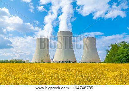 Thermal power plant with rape field, cloudy sky