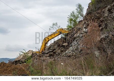Part of excavator behind the slope. Yellow hydraulic bucket.