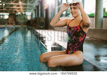 Female Swimmer Sitting At The Edge Of A Pool