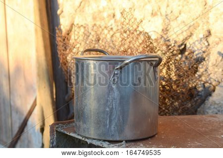 Stainless steel pot on the street in the village on the background of the shed