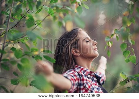 Attractive young brunette woman standing among leaves and branches in a forest with her eyes closed and arms raised up to embrace nature