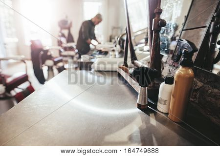 Hairdresser tools on counter with barber in background. Barber shop with hairstyling equipments