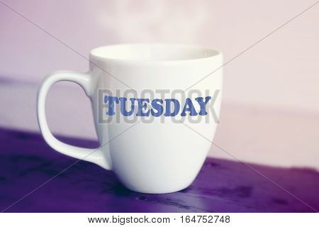 white cup with the word Tuesday on it on purple wooden table