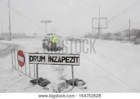 Bucharest Romania January 25 2016: A policeman is staying next to a closed road during a blizzard in Bucharest.