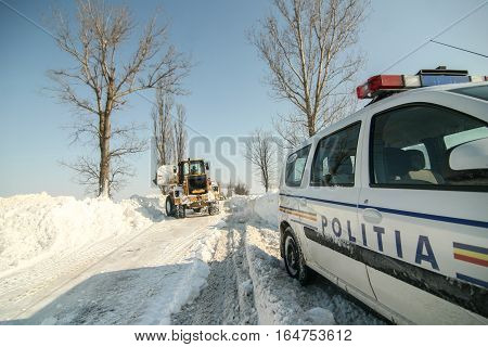 Bucharest Romania January 28 2012: A road sweeping vehicle clears snow from a road near a police car outskirts Bucharest.