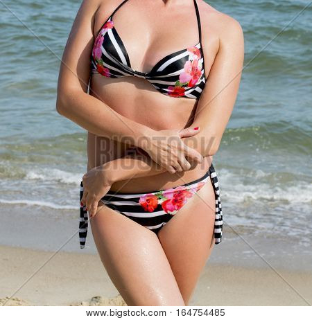 the woman's body in a bathing suit by the sea a subject rest the sea a holiday