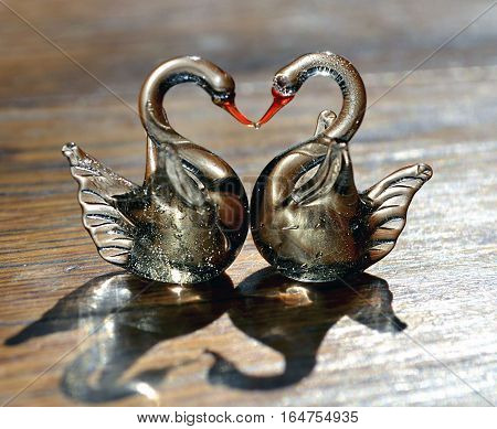Two glass swans with necks forming a love heart shape.Figurine glass swans on wooden background.Saint Valentine background with two swans in love.Valentines day or love concept.Selective focus.