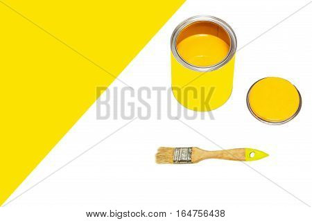 Bank of yellow paint and paintbrush on white background with empty space for text.