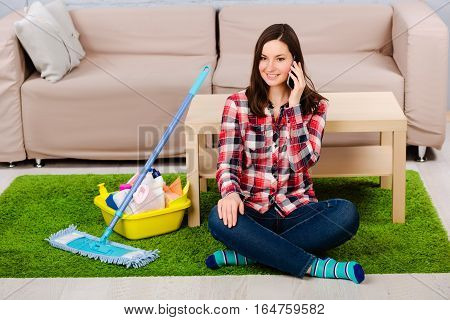 Young woman housewife dressed in casual clothing, sitting on the floor and talking on the phone. Beside her detergents to clean the house. Rest after the successful cleaning of the room