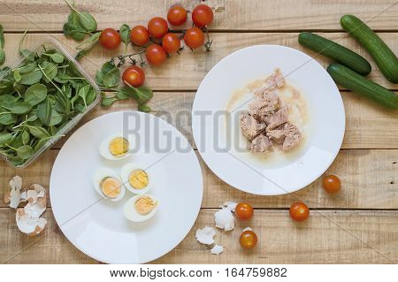 Top view of ingredients for healthy and balanced tuna salad. Tuna fish boiled eggs bunch of red cherry tomatoes and spinach leaves