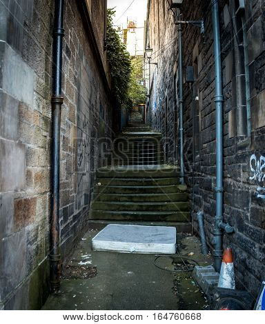 Narrow alleyway in Edinburgh with a matress