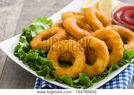 Fried calamari rings with lettuce and ketchup on wooden background