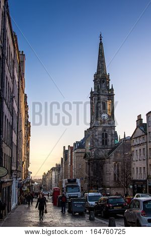 Edinburgh Scotland UK - 16 November 2016: Early morning traffic and people walking in Edinburgh's old town by Tron Kirk tower near St Giles Cathedral
