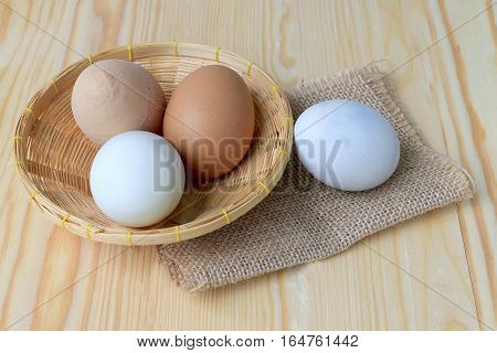 Chicken Eggs And Duck Eggs In Basket On A Wooden Table Background.