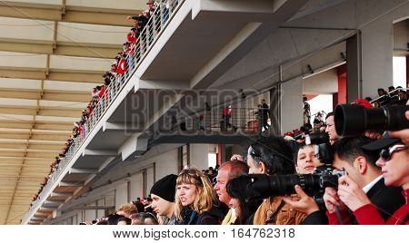 ISTANBUL/TURKEY-MAY 8, 2011 : People watching the race from the grandstand at the race track of Istanbul Park Circuit. Race cars are driving around the circuit at high speed.