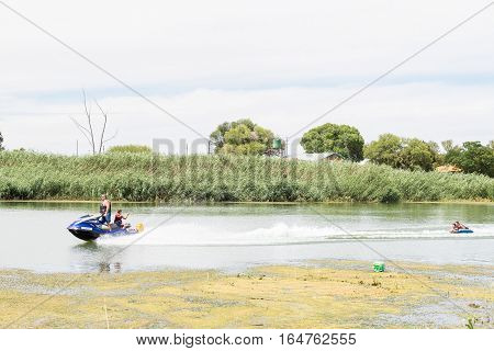 RITCHIE SOUTH AFRICA - DECEMBER 24 2016: Unidentified people on a jetski towing people on an inner tube on the Riet River (reed river) at Ritchie a small town in the Northern Cape Province