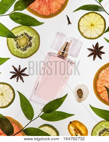 The bottle of pink perfume lie on the white background with different kinds of fruits and green leaves around the bottle.