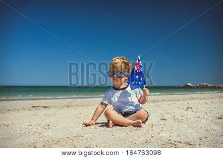 Cute cheaky boy with flag of Australia sitting on the sand at the beach celebrating Australia Day